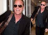 Well he DOES play a spy! Kiefer Sutherland goes incognito in all-black and sunglasses as he arrives at LAX