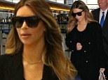 Off to join Kanye? Kim Kardashian hides beneath an all-black ensemble as she breezes through LAX en route to Europe