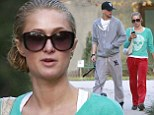 The wet look: Paris Hilton slicks back her hair into a low bun to walk her dogs with boyfriend River Viiperi