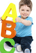 Cute boy holding giant letters - education