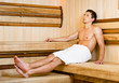 Half-naked young man relaxing in sauna