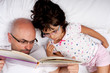 father and daughter reading a book in bed