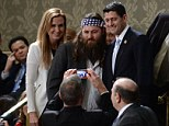 Willie Robertson (C) of the television show Duck Dynasty poses for a picture with US Repubklican Representative from Wisconsin Paul Ryan (R) and his wife Janna Ryan before US President Barack Obama delivers his State of the Union