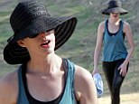 We can see you! Anne Hathaway hides porcelain skin under big floppy black hat while hiking in LA