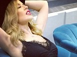 Kylie Minogue poses seductively in a lacy black bra