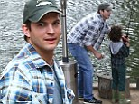 Fishing fun: Two And A Half Men actor Ashton Kutcher teaches a young boy how to fish in Malibu, California