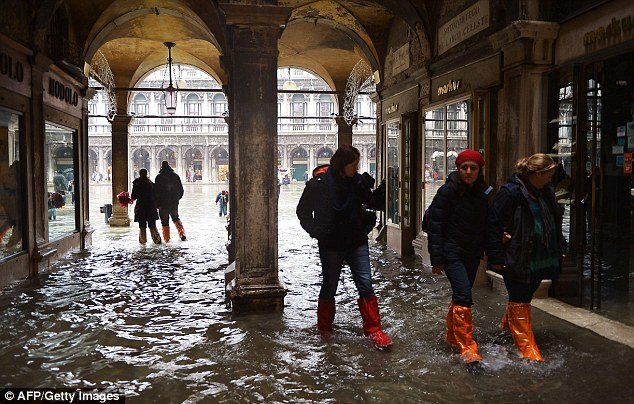 Tourists don waterproof boots as they wade their way across flooded St Mark's Square