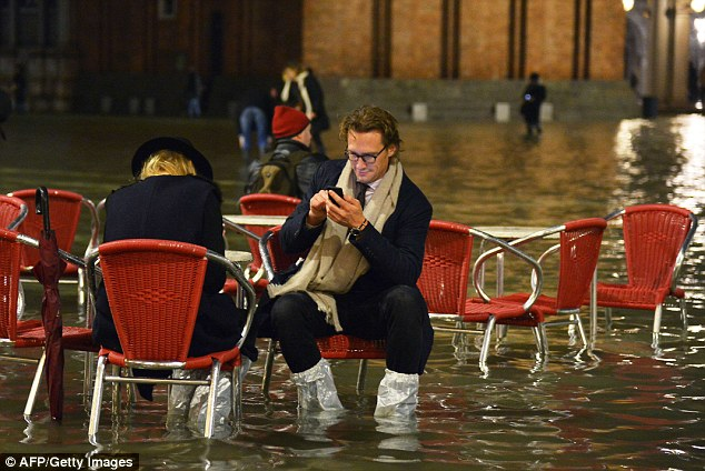 A couple pauses to take a seat as they wade their way across the square. Currently, a third of the city is underwater
