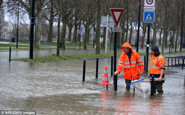 City employees walk in a flooded street, on the right bank of the Garonne river in Bordeaux, western France