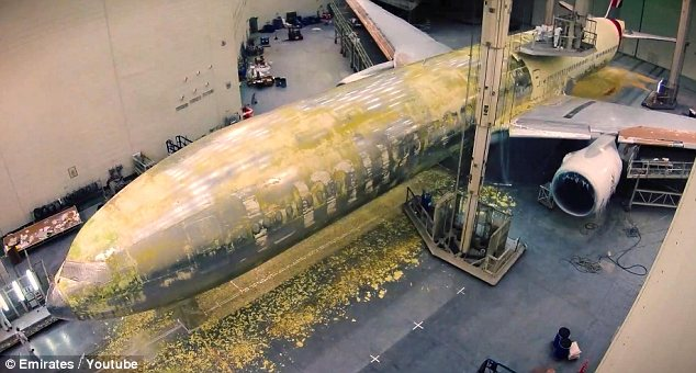 Half-way: The plane has lost most of its paint by this point as the work continues around the clock