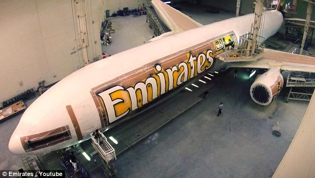 Stencil: Next the name of the airline is reapplied to the Boeing jet by workers