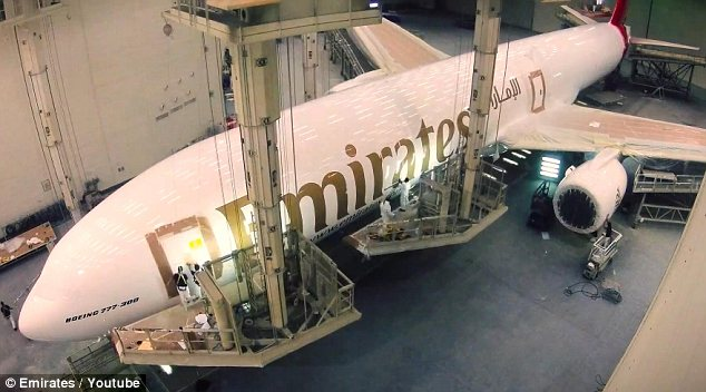 Nearly done: The painting crew put the finishing touches to the plane as they work on the door
