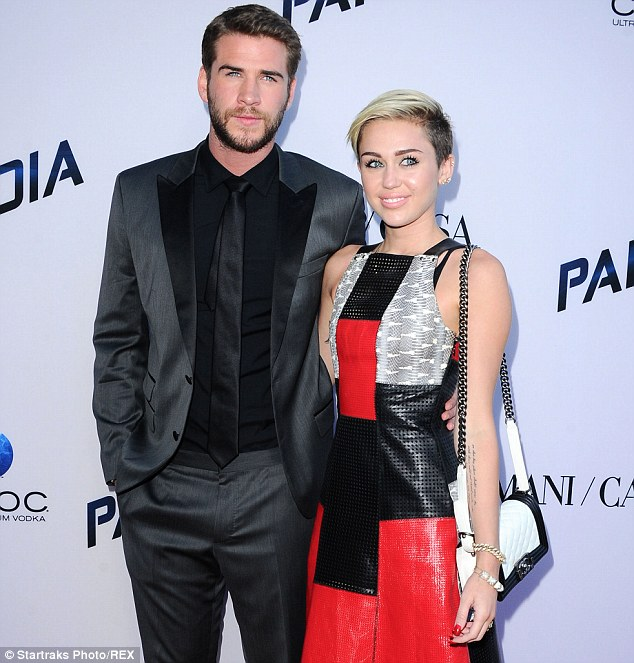 They go back: Cyrus, seen here with Hemsworth in August, said she's know the actor since she was 16-years-old