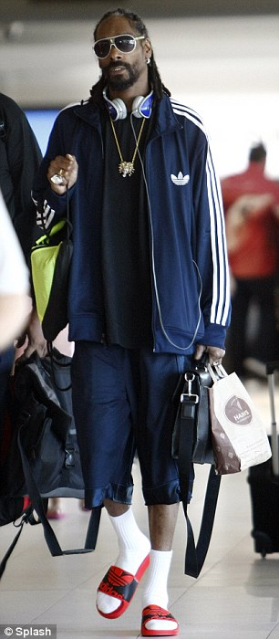 Dressing like it's hot: For this flight the iconic Californian rapper wore his signature Adidas tracksuit matching ensemble but as it is summer swapped his long pants out for shorts