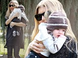 Baby's first Super Bowl party! Fashionable Fergie gives her NFL jersey a feminine makeover but five-month-old Axl steals the show in cute football beanie