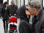 Put her down! Alec Baldwin grabs Spanish born wife Hilaria for a kiss as they stroll with baby Carmen through wintry Madrid