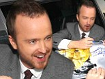 A man of the people! Aaron Paul grins as he signs Breaking Bad posters for fans in New York City after busy Super Bowl weekend