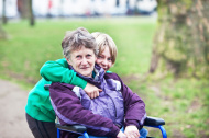 young carer out with his grandmother in a wheelchair