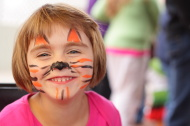 little girl smiles at camera, face painted like tiger
