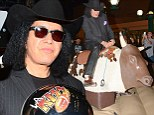 Ride 'em cowboy! KISS rocker Gene Simmons good naturedly agrees ride a mechanical bull at a rodeo event Saturday in Anaheim, California