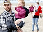 Not exactly beach weather! Jack Osbourne bundles up wife and daughter for a chilly family day on the sand in Malibu