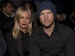 Serious about their fashion: Front row love birds Sam Worthington and Lara Bingle barely raise a smile as they watch Alexander Wang's catwalk show