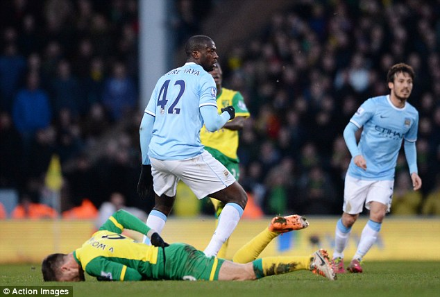 Ouch: Van Wolfswinkel lies clutching his back on the ground after the incident with Toure (centre)