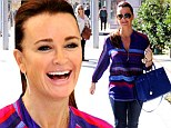 She's sure chipper! Kyle Richards brightens up in red and purple striped top on the way to her boutique