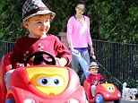 Go Speed Racer! Alessandra Ambrosio is the doting mom as she lets her son Noah do the steering on neighborhood stroll