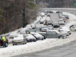 Clear up: On Thursday, police and wrecker crews work to remove dozens of vehicles that were either parked or abandoned in Raleigh, North Carolina as residents tried to get home during Wednesday's storm