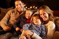 Portrait family relaxing at home by firelight