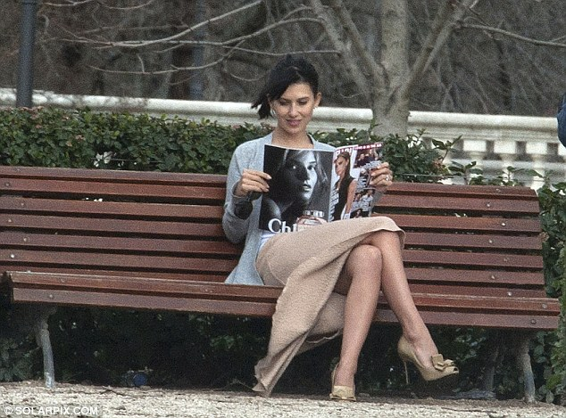 Taking a breather: The fashion-savvy Hilaria sat on a bench leafing through a Spanish magazine