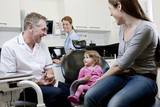 A male dentist with a little girl patient and her mother