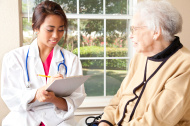 Healthcare Professional Writing on Patient Records With Senior A