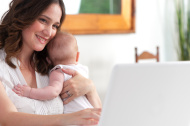 Mother using laptop with baby looking happy