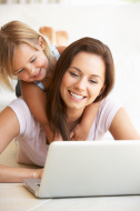 Young mother and daughter using laptop computer