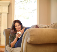 Beautiful woman resting on sofa holding a cup of coffee