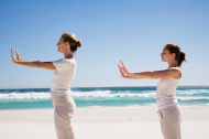 Two women exercising yoga on beach