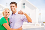 Couple With Keys Standing In Front Of New House