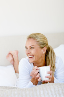 Mature woman lying in bed laughing