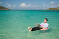 Businessman Floats Outdoors in Tropical Sea Working on Laptop