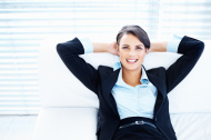 Business woman on couch with hands behind head