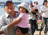 Daddy's girl! Bruce Willis plays on the beach with his one-year-old daughter Mabel and pregnant wife Emma Heming