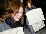 Life in the fast lane! Julianne Moore is barefaced and flawless as she glides through JFK with expensive designer garment bag