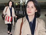 First class style: Michelle Dockery looked chic in a beige trench coat at Heathrow Airport