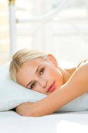 Portrait of beautiful smiling woman on bed at bedroom