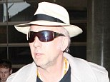 50 Shades Of Cage! Nicolas shows off grey head of hair underneath fedora while arriving at LAX