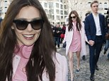 Elizabeth Olsen shows off her toned legs in a pretty pink dress as she clings to boyfriend Boyd Holbrook at Paris Fashion Week