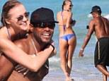 Snap happy! Singer Maxwell looks like the cat that got the cream as he photographs bikini-clad model girlfriend Deimante Guobyte during beach frolic