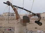 Horror: The body of a man accused of spying for the U.S. is seen tied to a football goal post outside al-Shihr city in Hadhramout, Yemen